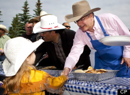 Prime Minister Stephen Harper, right, shakes hands with Ashleigh Budd, four, as he dishes out pancakes at Stampede breakfast in Calgary, Alta., Sunday, July 10, 2011.THE CANADIAN PRESS/Jeff McIntosh