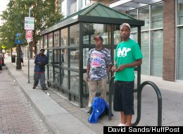 Raymond Parker, 61, and Michael Smith, 20, wait for a bus at Mack and Woodward in Detroit on July 14.