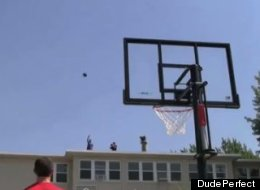 Members of the group Dude Perfect and Team USA toss a basketball from the roof of a building into a hoop.