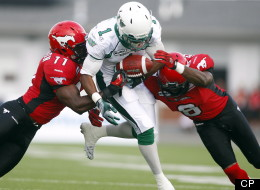 Saskatchewan Roughriders' Kory Sheets, centre, tries to run the ball past Calgary Stampeders' Malik Jackson, left, and Fred Bennett during first quarter CFL football action in Calgary, Alta., Thursday, July 19, 2012. (THE CANADIAN PRESS/Jeff McIntosh)