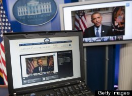President Barack Obama participates in an interview with YouTube and Google from the Roosevelt Room of the White House in Washington, DC, January 30, 2012, as seen on a laptop in the Brady Press Briefing Room. (Saul Loeb / Getty)