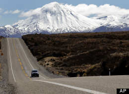 A car drives state highway 1 near the snowcapped mountains at Tongariro National Park in New Zealand, Wednesday, Sept. 28, 2011. (AP Photo/Christophe Ena)