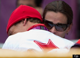 Canada's Simon Whitfield is hugged by his wife after crashing and retreating from the men's triathlon at Hyde Park during the Summer Olympics in London on Tuesday, August 7, 2012. (CP/Sean Kilpatrick)