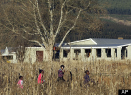 In this photo taken Monday, Aug. 8, 2011, children walk past the Umvoti AIDS Centre in Greytown, South Africa. The words of little children from an isolated town in rural South Africa may have stopped an international sex predator. U.S. investigators say Jesse Osmun confessed that as a Peace Corps volunteer, he for months sexually molested at least five girls at a South African shelter for AIDS orphans and other children. (AP Photo/Themba Hadebe)