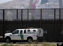 A Border Patrol agent drives his white and green vehicle in front of the fence separating Tijuana, Mexico, behind, and San Diego, Friday, June 22, 2012. (AP Photo/Gregory Bull)