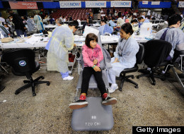 California gears up for the ACA changes in 2014. Pictured: dental volunteers give free services to underserved Angelenos. (AP)