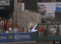 Los Angeles Angels outfielder Vernon Wells falls over the wall as he chases down a fly ball during a game against the Texas Rangers.
