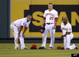 Los Angeles Angels left fielder Vernon Wells, left, center fielder Mike Trout, center, and right fielder Torii Hunter wait for a pitching change during the eighth inning of their baseball game against the Texas Rangers, Wednesday, Sept. 19, 2012, in Anaheim, Calif.