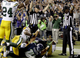 Officials signal a touchdown by Seattle Seahawks wide receiver Golden Tate, obscured, on the last play of an NFL football game against the Green Bay Packers, Monday, Sept. 24, 2012, in Seattle. The Seahawks won 14-12.