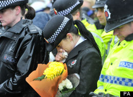 A police officer bows her head at the vigil for her murdered colleagues