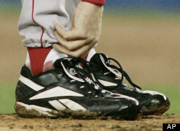 In this Oct. 19, 2004 file photo, Boston Red Sox pitcher Curt Schilling tends to his right ankle during the third inning of game 6 of the ALCS against the New York Yankees in New York.