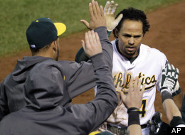 Oakland Athletics' Coco Crisp celebrates in the dugout after scoring on a double by Stephen Drew in the sixth inning of Game 4 of their American League division baseball series against the Detroit Tigers in Oakland, Calif., Wednesday, Oct. 10, 2012.