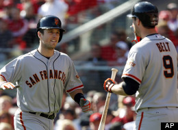 San Francisco Giants' Buster Posey is congratulated by Brandon Belt after Posey hit a grand slam against the Cincinnati Reds in the fifth inning of Game 5 of the National League division baseball series, Thursday, Oct. 11, 2012, in Cincinnati.