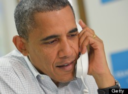 U.S. President Barack Obama speaks on the phone to a volunteer during an unannounced visit to a campaign office October 14, 2012 in Williamsburg, Virginia. (MANDEL NGAN/AFP/GettyImages)