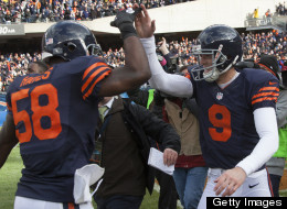 Robbie Gould of the Chicago Bears celebrates kicking a game-winning field goal on the Carolina Panthers with teammate Geno Hayes on October 28, 2012 at Soldier Field in Chicago, Illinois.