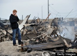 Gavin Byrne views damage in the Breezy Point area of Queens, New York on October 30, 2012 after fire destroyed about 80 homes as a result of Hurricane Sandy, which hit the area the day before.