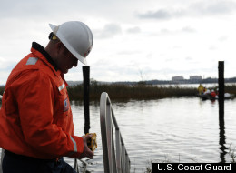 Petty Officer 1st Class Sean Stone, a response technician from the Atlantic Strike Team, monitors air quality with a gas analyzer near a Motiva facility while clean-up crews remove oily waste and debris caused by Hurricane Sandy near Linden, N.J., Oct. 31, 2012.