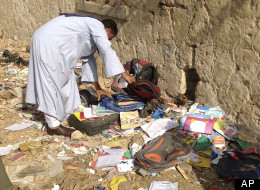 An Egyptian looks through books and school bags that were strewn along the tracks at the scene where a speeding train crashed into a bus carrying children to their kindergarten, killing at least 47, officials said, near Assiut in southern Egypt, Saturday, Nov. 17, 2012. (AP Photo/Mamdouh Thabet)