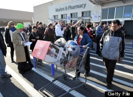 Shoppers walk past people who support Walmart workers as they protest working conditions at the company in front of a Walmart Superstore on November 23, 2012 in Secaucus, New Jersey. (STAN HONDA/AFP/Getty Images)