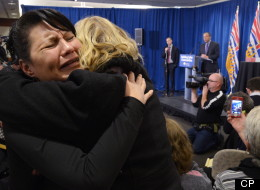 Women hug as Commissioner Wally Oppal (background) delivers the final report of the Missing Women Inquiry in Vancouver, Monday, Dec.17, 2012. (THE CANADIAN PRESS/Jonathan Hayward)