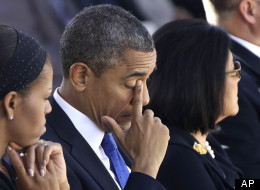 President Barack Obama wipes his eye as he and first lady Michelle Obama attend the Memorial Service for Sen. Daniel Inouye, D-Hawaii, at the Punchbowl National Memorial Cemetery of the Pacific in Honolulu, Sunday, Dec. 23, 2012. Right is Inouye's wife, Irene Inouye. (AP Photo/Gerald Herbert)