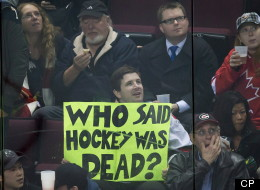 A hockey fan holds up a sign as Team WHL and Team Russia play during the third period in game 5 of the CHL Subway Super Series in Vancouver, B.C., on November 14, 2012. Fans filling the NHL hockey void with football and movies are welcoming its return.THE CANADIAN PRESS/Darryl Dyck