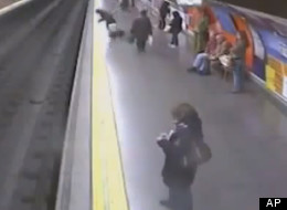 Closed-circuit television cameras captured dramatic images of a Spanish police officer saving a woman from the subway tracks in the Madrid underground as a train was about the enter the station