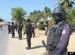State police stand at a roadblock due to stepped up security after masked armed men broke into a beach home, raping six Spanish tourists who had rented the house in Acapulco, Mexico, Tuesday Feb. 5, 2013. According to the mayor of Acapulco, five masked men burst into a house the Spaniards had rented on the outskirts of Acapulco, in a low-key area near the beach, and held a group of six Spanish men and one Mexican woman at gunpoint, while they raped the Spanish women before dawn on Monday. (AP Ph