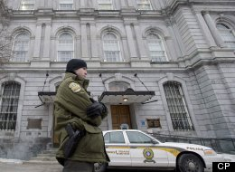 A Sûreté du Québec officer stands outside City Hall in Montreal, Tuesday, Februray 19, 2013, during a raid by officers on the premises. THE CANADIAN PRESS/Graham Hughes.